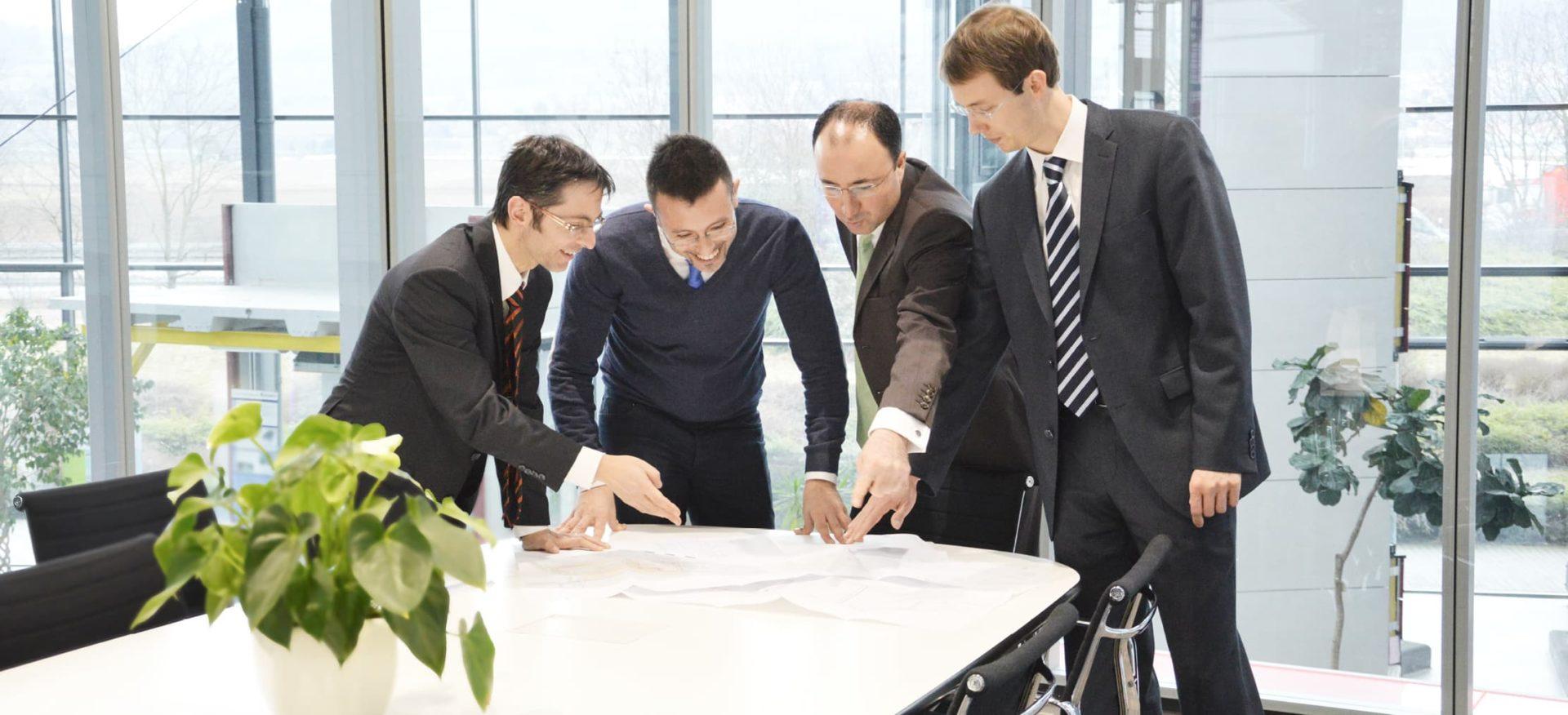 Ein Team von vier Männern diskutiert Baupläne