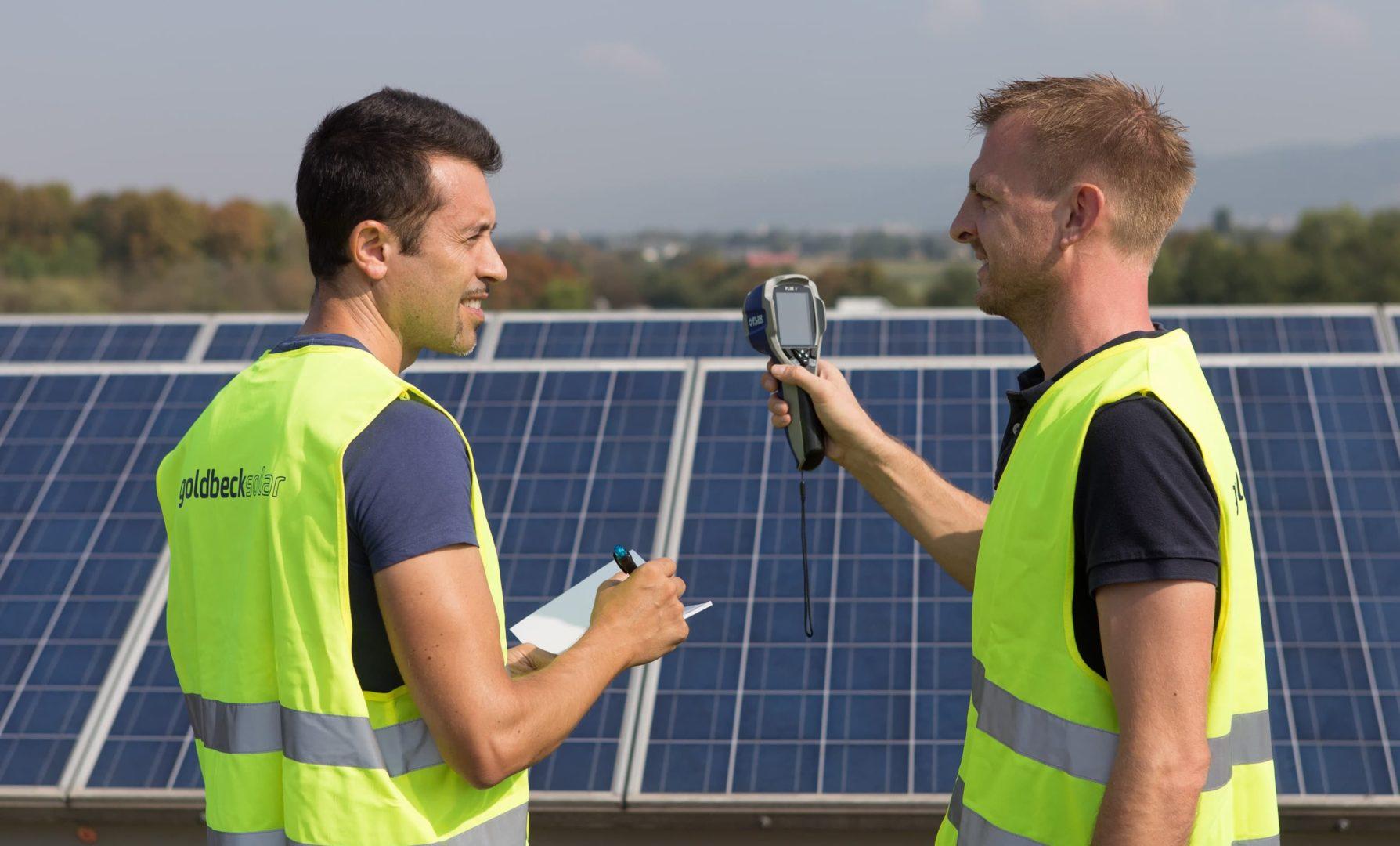 Zwei Ingenieure prüfen eine Solaranlage.