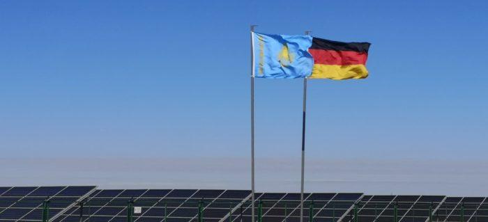 Die Flagge von Kasachstan und von Deutschland vor Solarmodulen