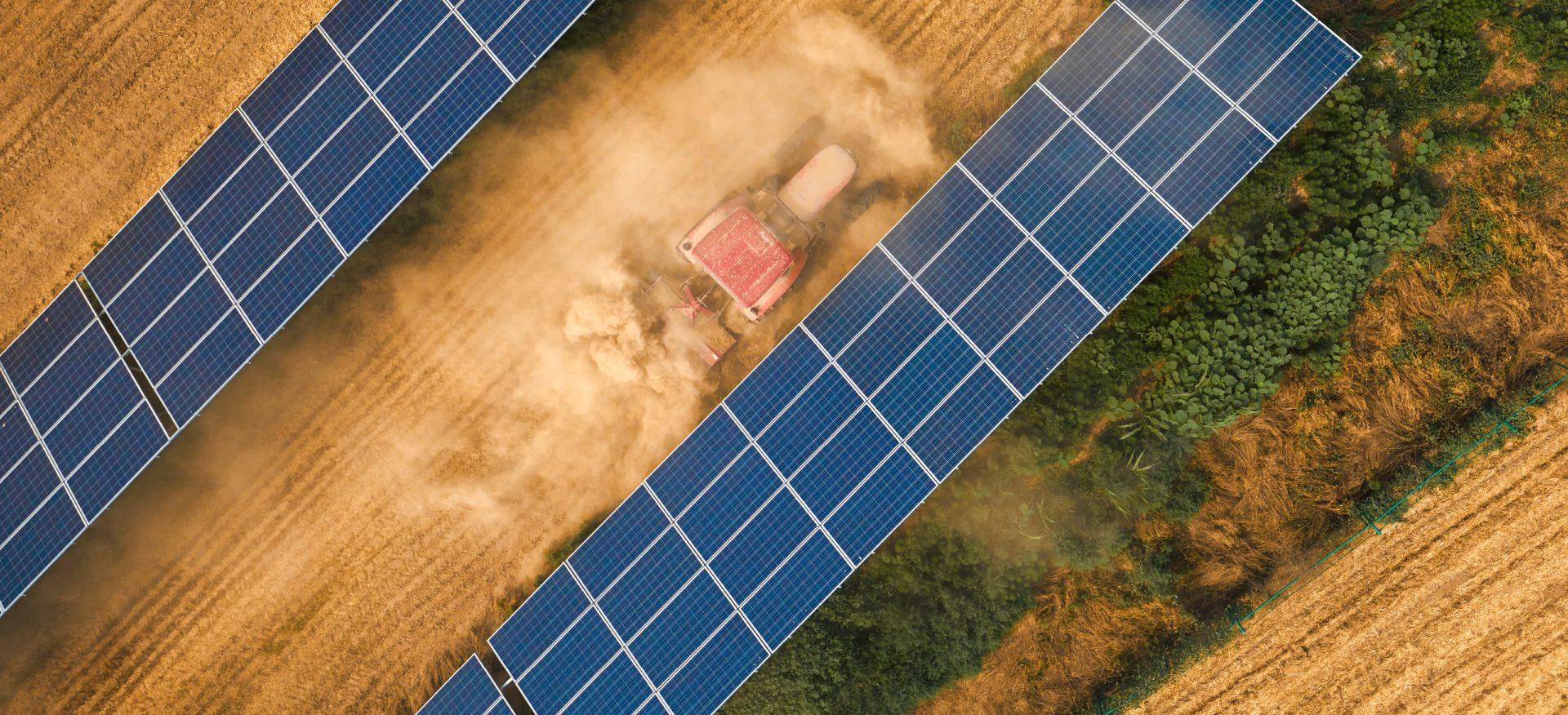 Ein Traktor zwischen Solarkollektoren und der Schriftzug Farm 5.0.