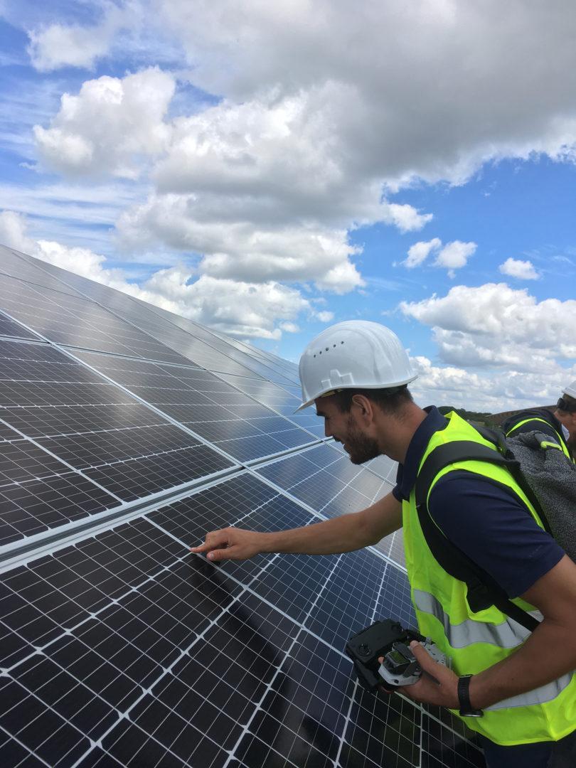 Mitarbeiter schaut sich Solarpaneele genau an