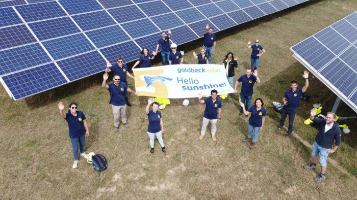 """Mitarbeiter von Goldbeck Solar mit einem Banner mi der Aufschrift """"Hello Sunshine"""""""