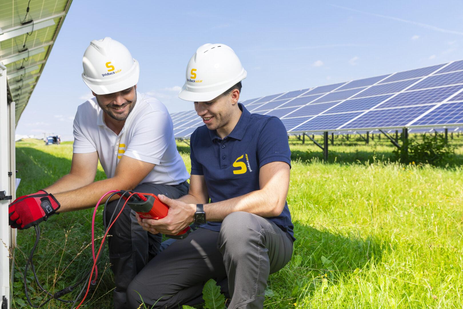 Zwei Mitarbeiter des O&M-Teams von Goldbeck Solar beim Prüfen einer Solaranlage. Die Person links trägt ein weißes Shirt, die Person rechts ein blaues Shirt mit Goldbeck-Solar-Logo. Beide tragen Helme.,